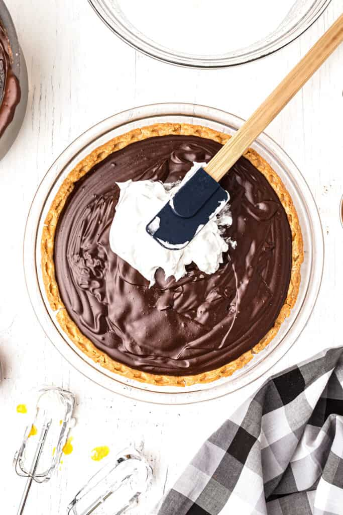 Spreading meringue on pie filling with a spatula.