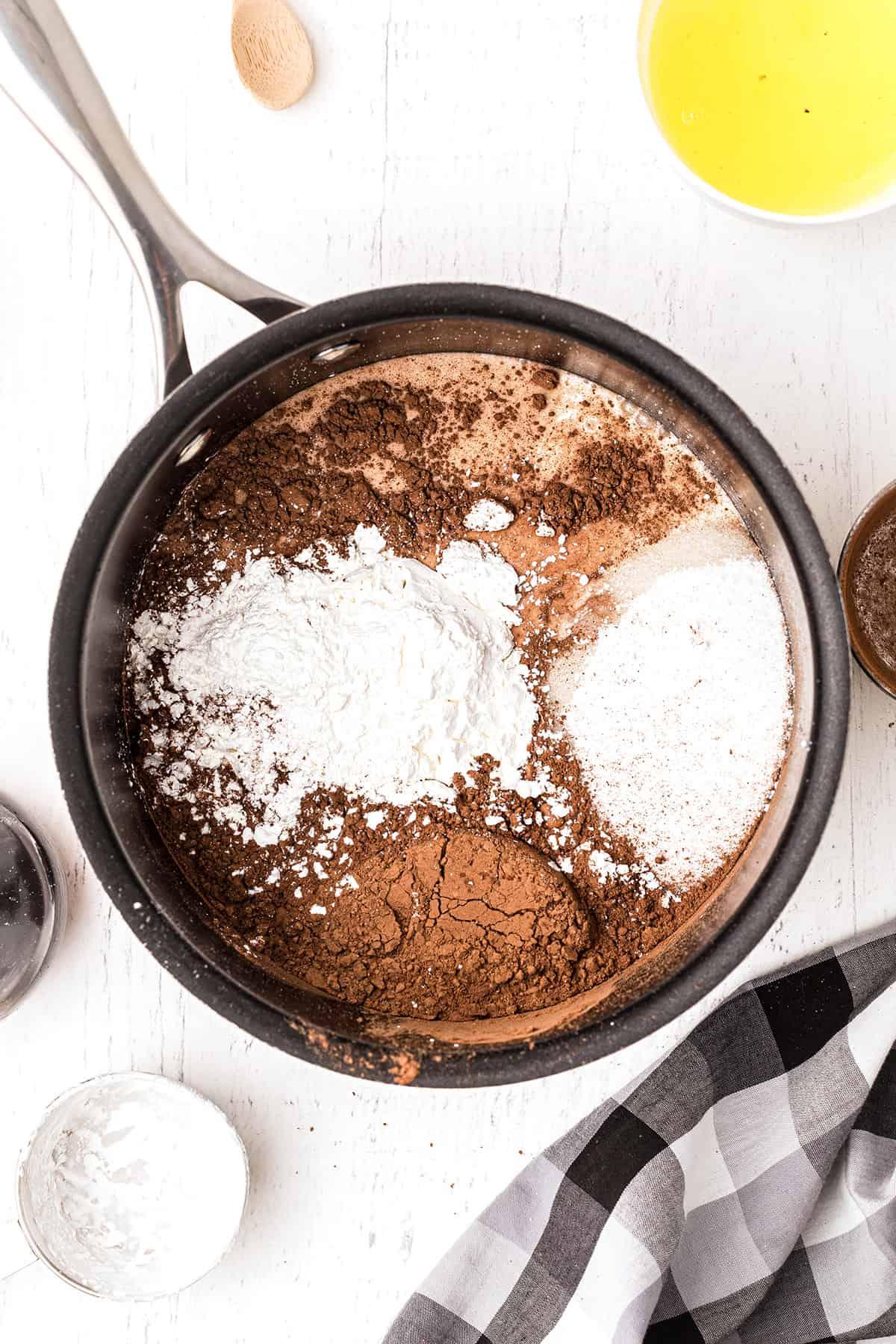 Medium saucepan with sugar, cocoa, salt and cornstarch.