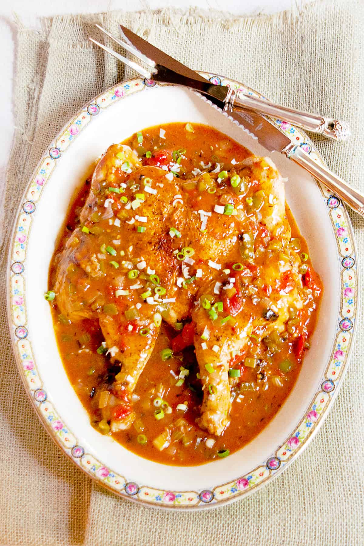 Creole Style Smothered Chicken presented on a large serving platter.