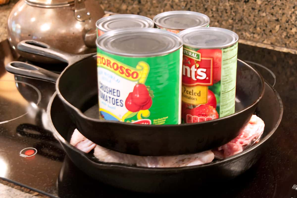 Smaller skillet with cans as weights on top of chicken in larger skillet.