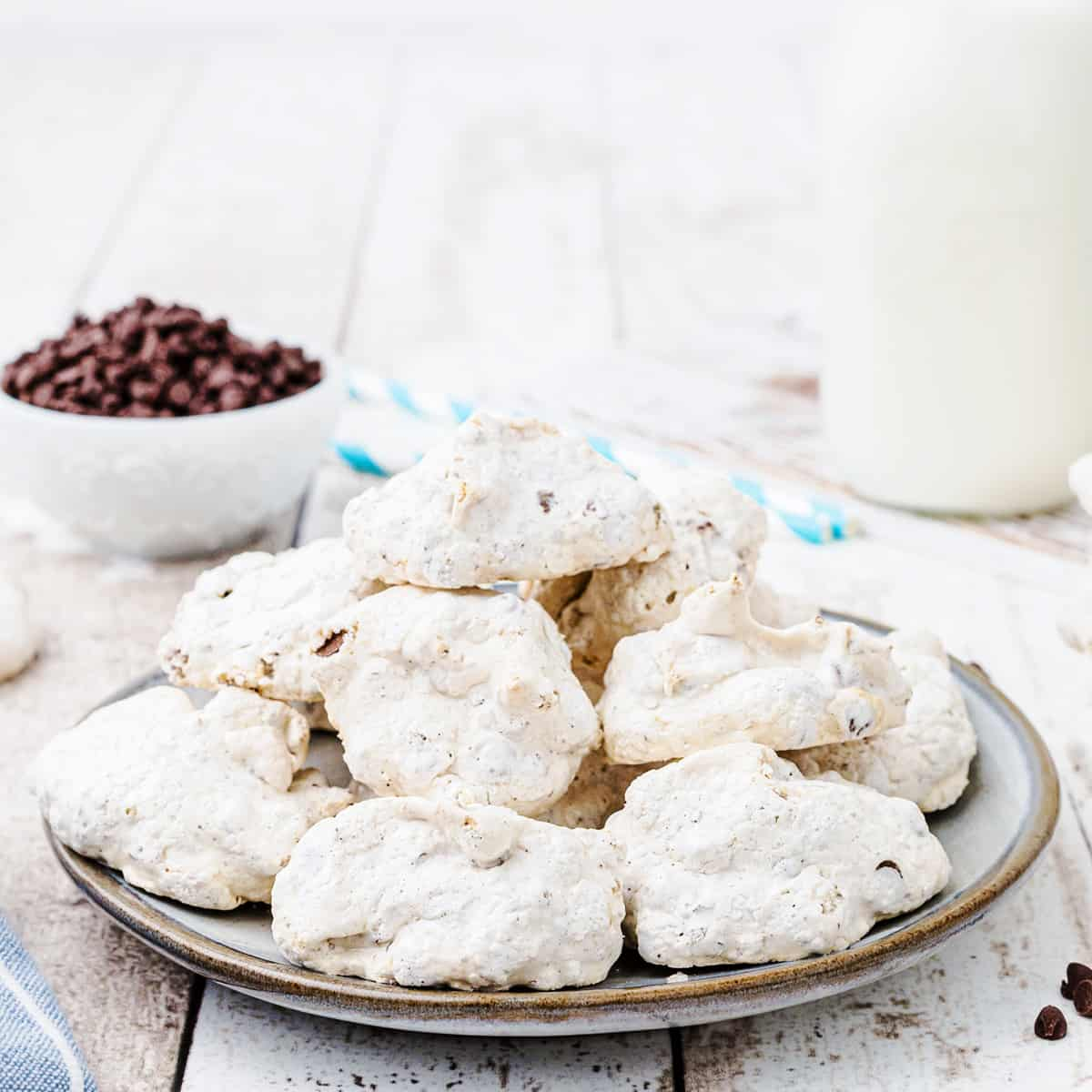 Forgotten cookies on a serving plate with milk and chocolate chips in the background.