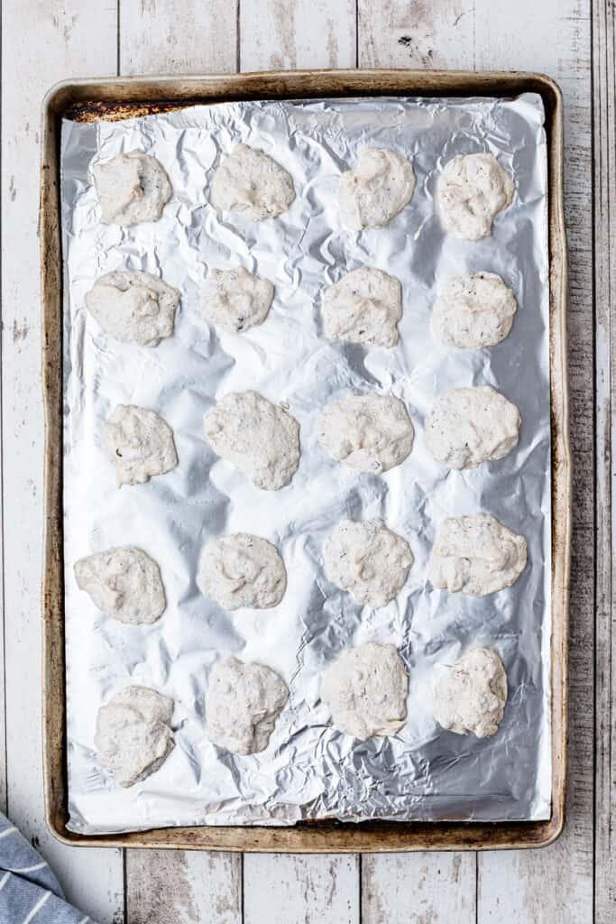 Full baking sheet of meringues ready for oven.