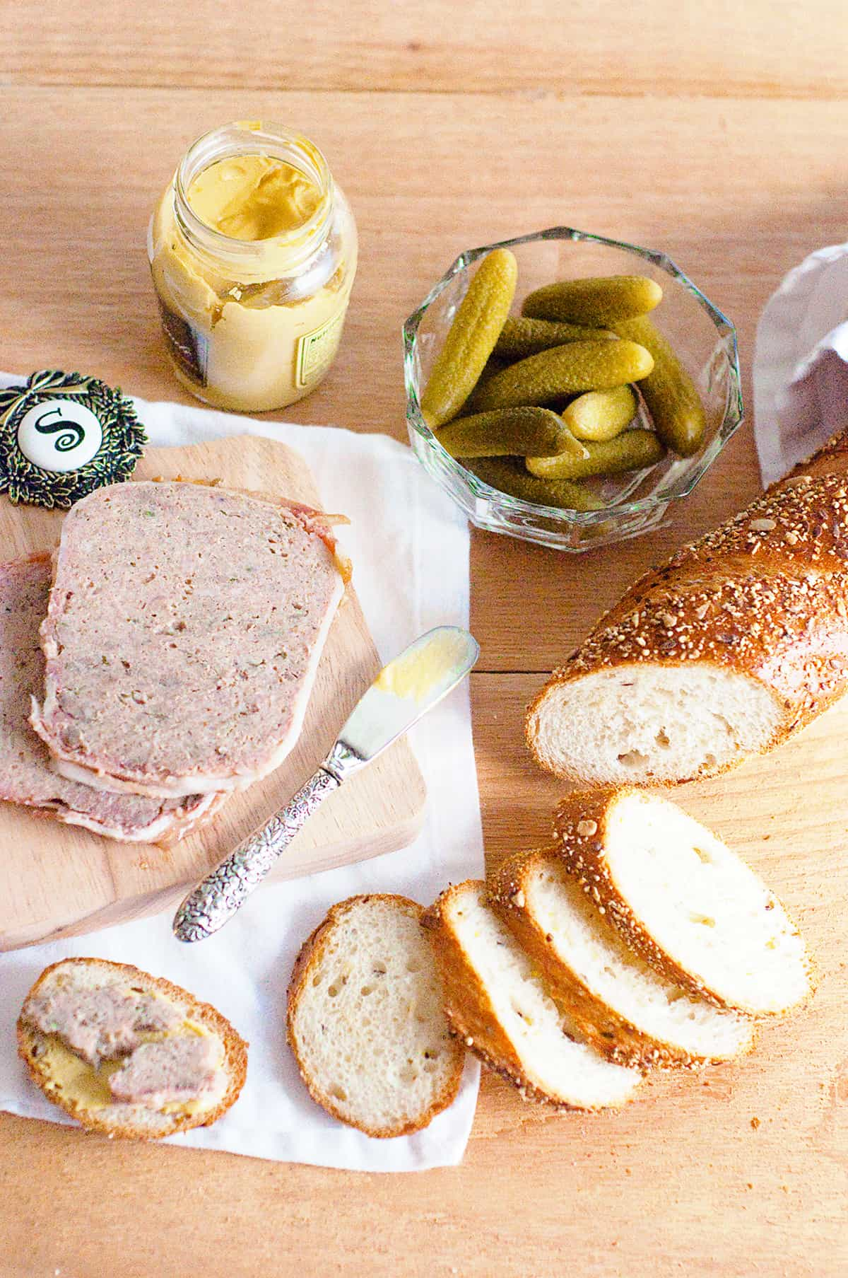 Sliced French country terrine on a serving board with sliced baguette, cornichons, and mustard.