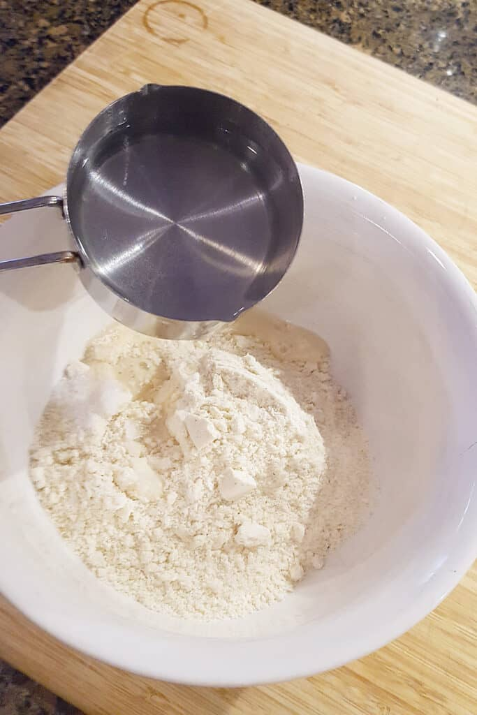 Pouring hot water into the cornmeal in a mixing bowl.