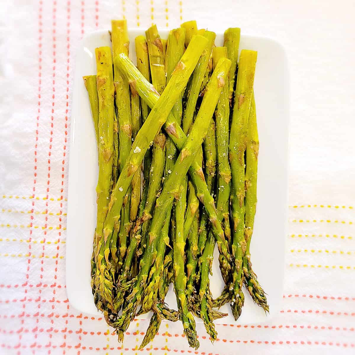 Oven roasted asparagus on a white serving dish.