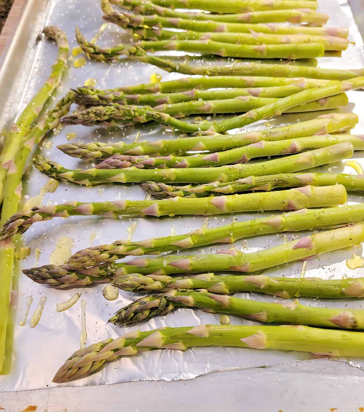 Asparagus on lined baking sheet drizzled with oil.