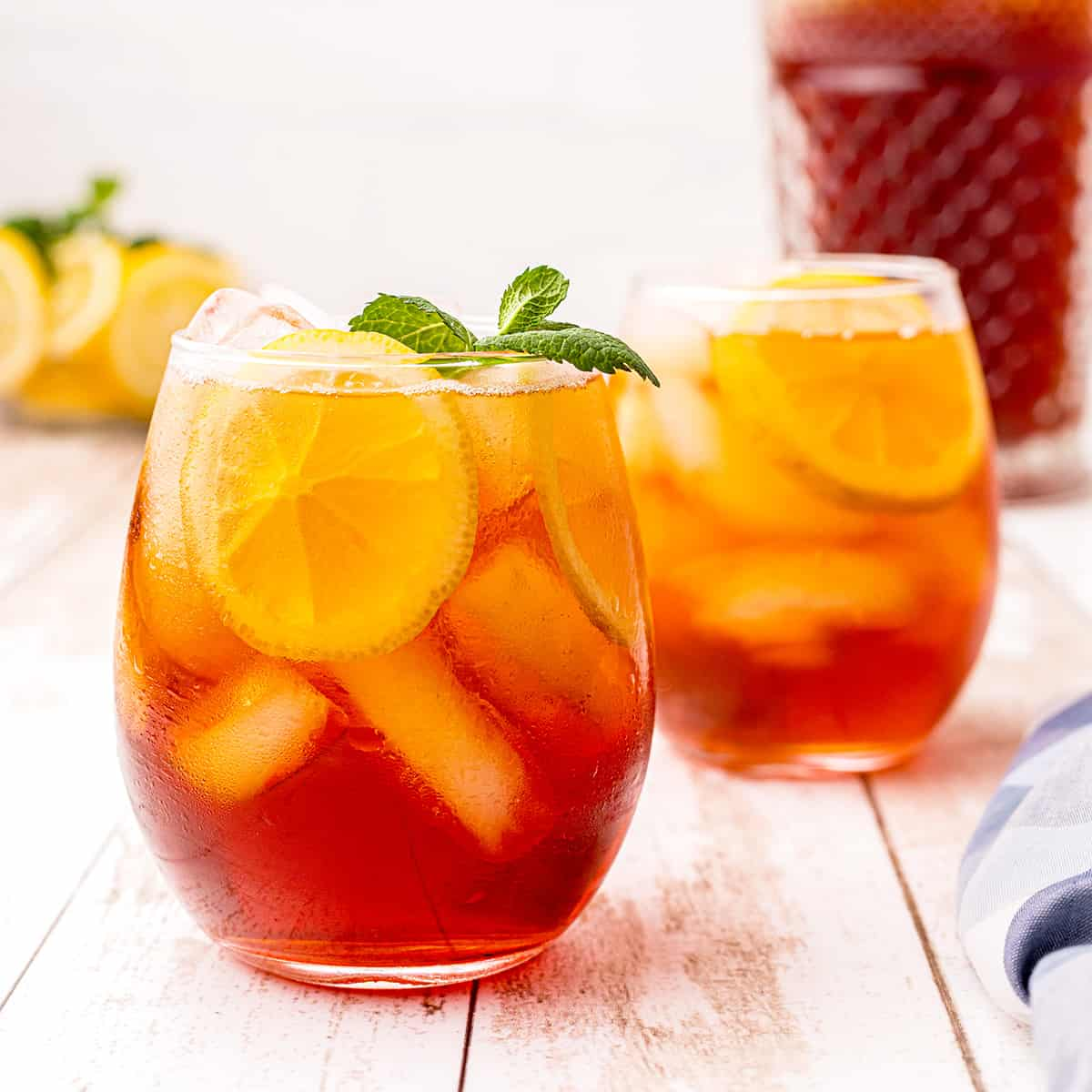 A glass of southern iced sweet tea with lemon and mint.