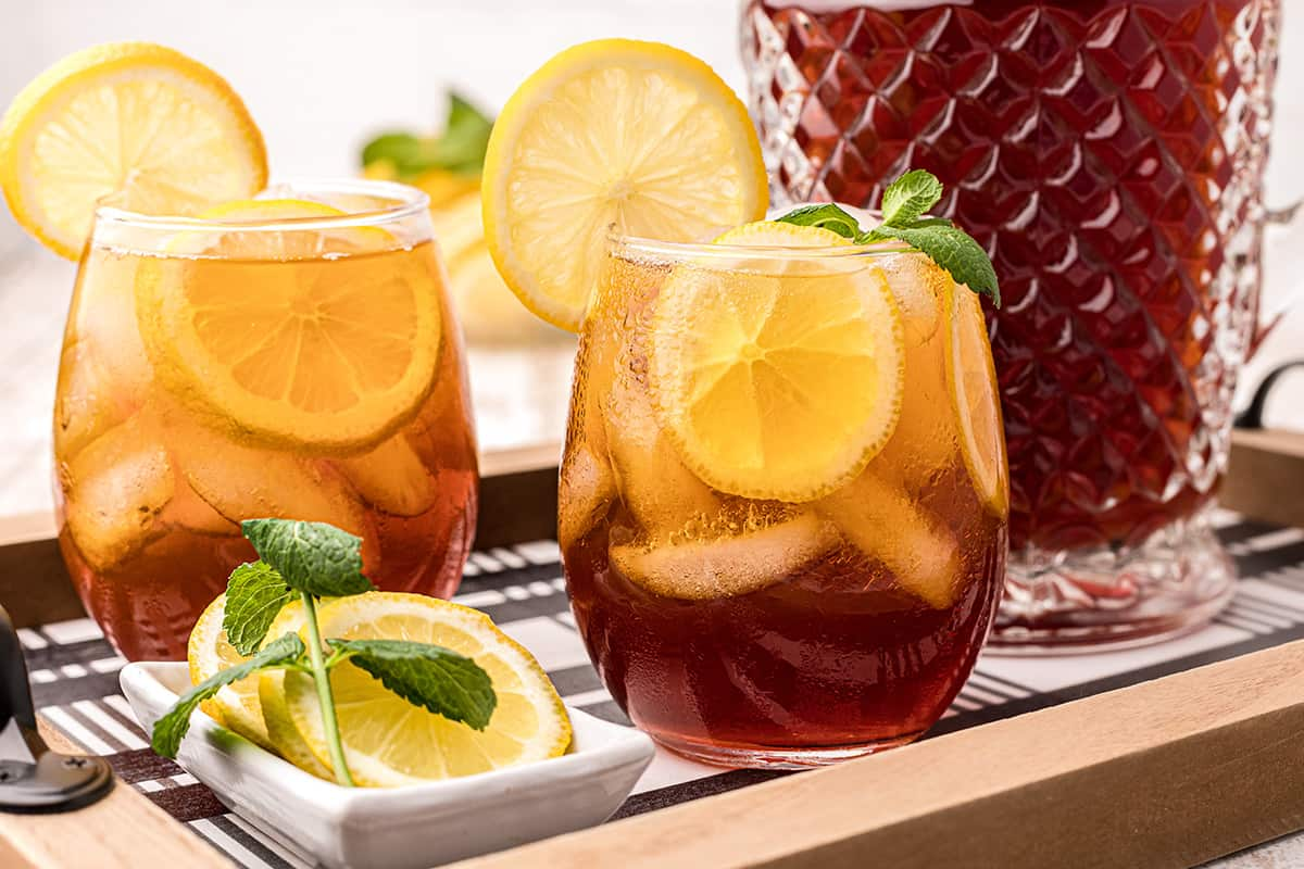 A glass of southern iced sweet tea with lemon and mint on a serving tray.