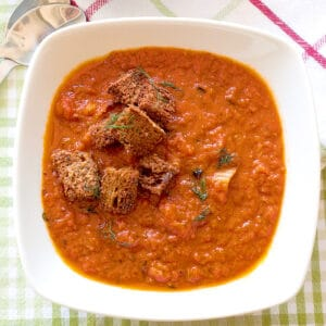 A bowl of tomato fennel soup with croutons on top.