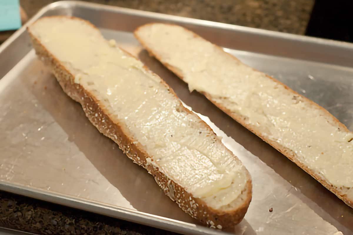 Split buttered loaf of Italian bread on a baking sheet.