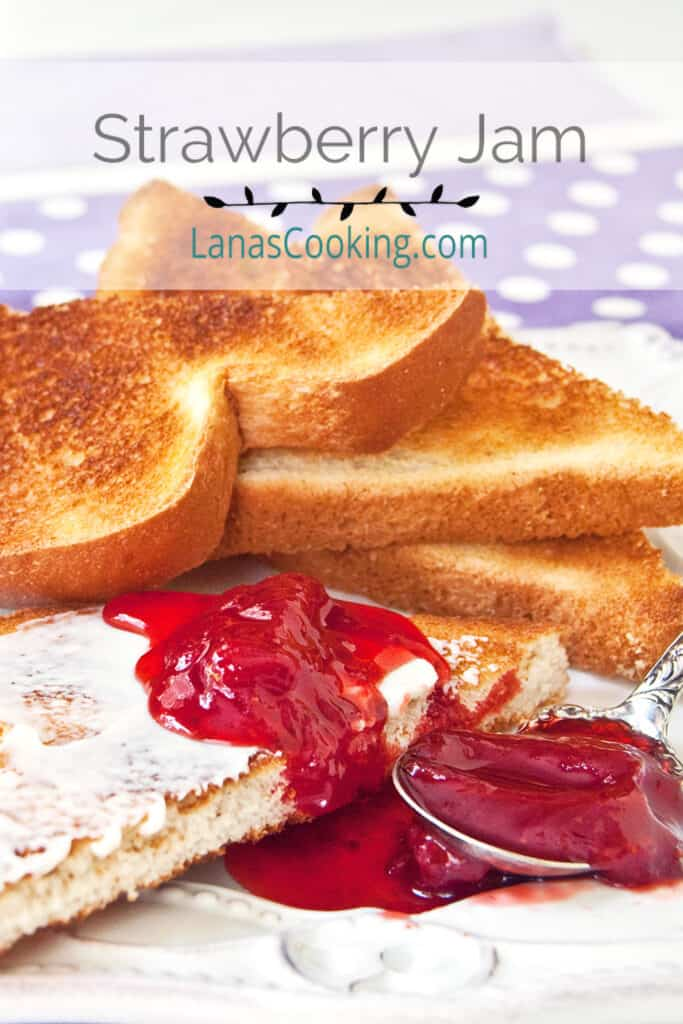 Strawberry jam on buttered toast with jars of jam in the background.