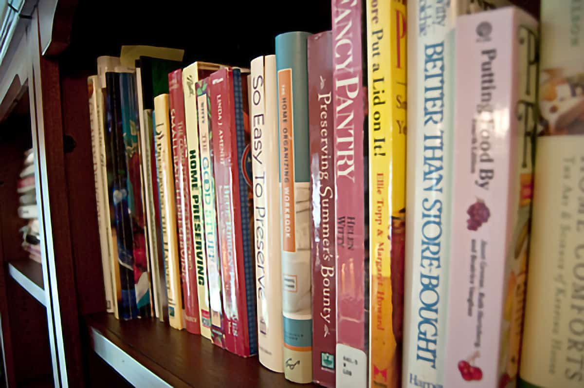 A row of canning reference books in a bookcase.