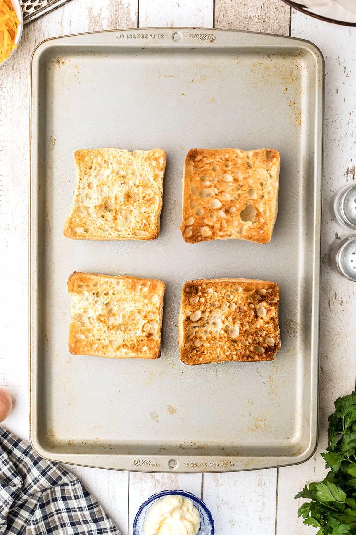 Toasted ciabatta rolls on a baking sheet.