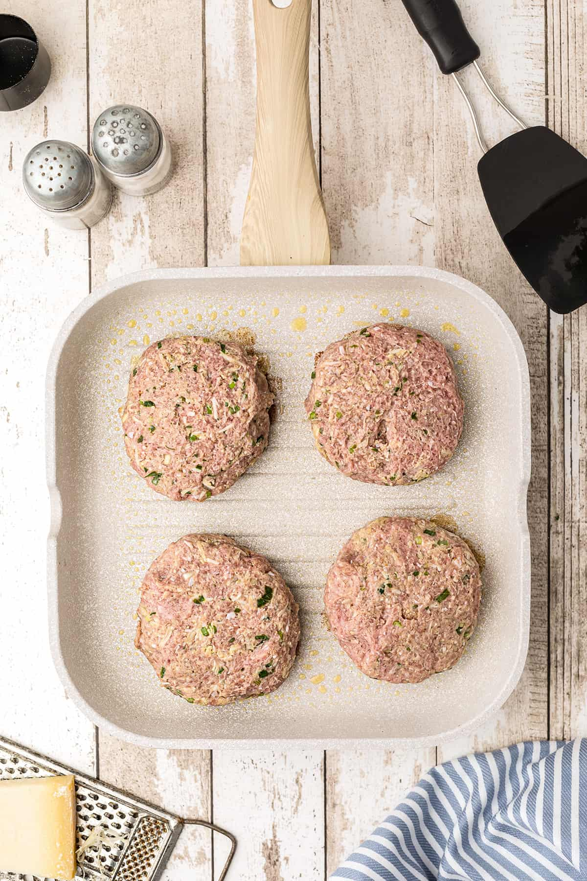Four burger patties cooking on a grill pan.
