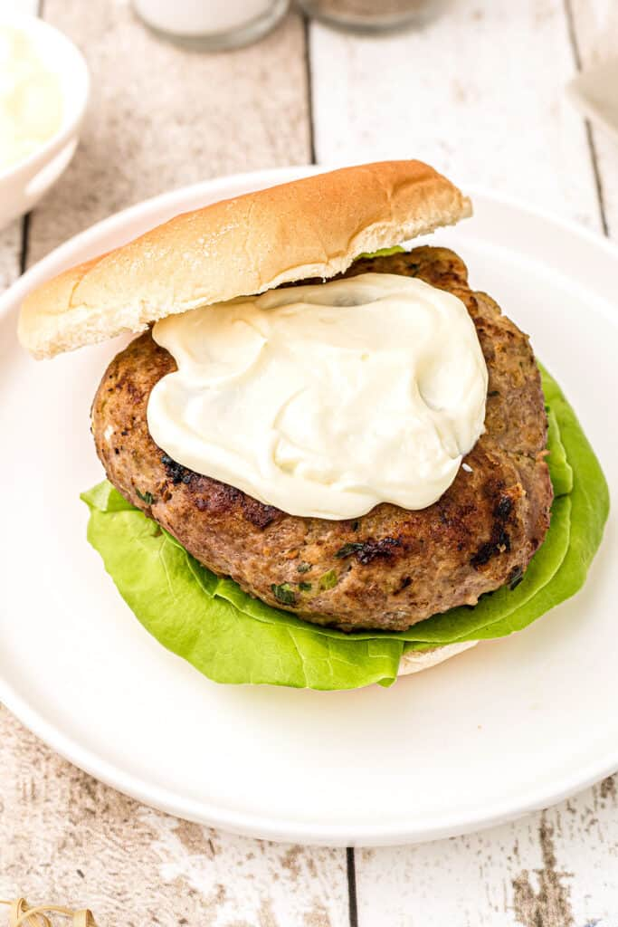 A turkey burger patty on a bun atop a white plate topped with mayonnaise.