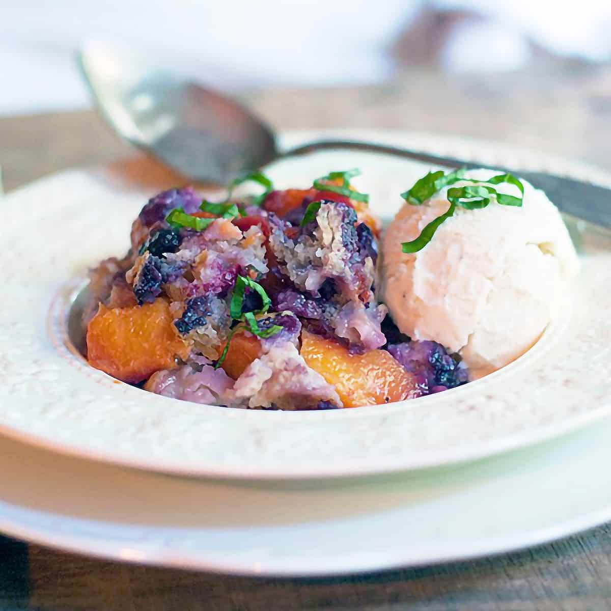 A serving of peach blueberry basil cobbler in a bowl with ice cream.