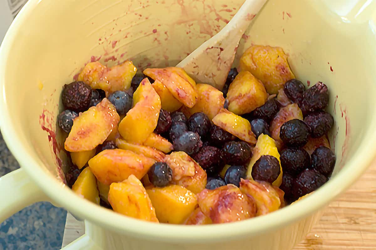 Peaches and blueberries in a mixing bowl.