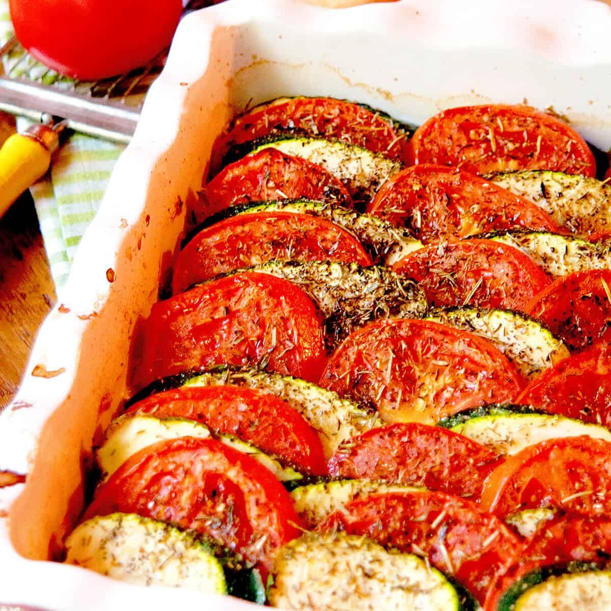 Finished tomato zucchini tian in a baking dish.