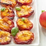 Grilled peach halves on a white serving plate.