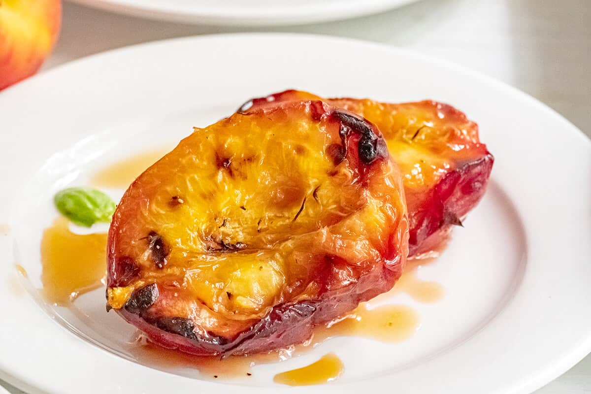 Grilled Peaches - halves on a white serving plate.