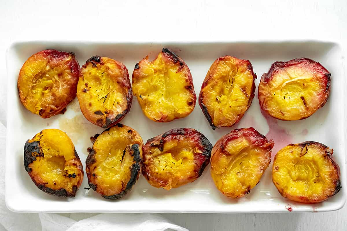 Grilled peach halves on a white platter.