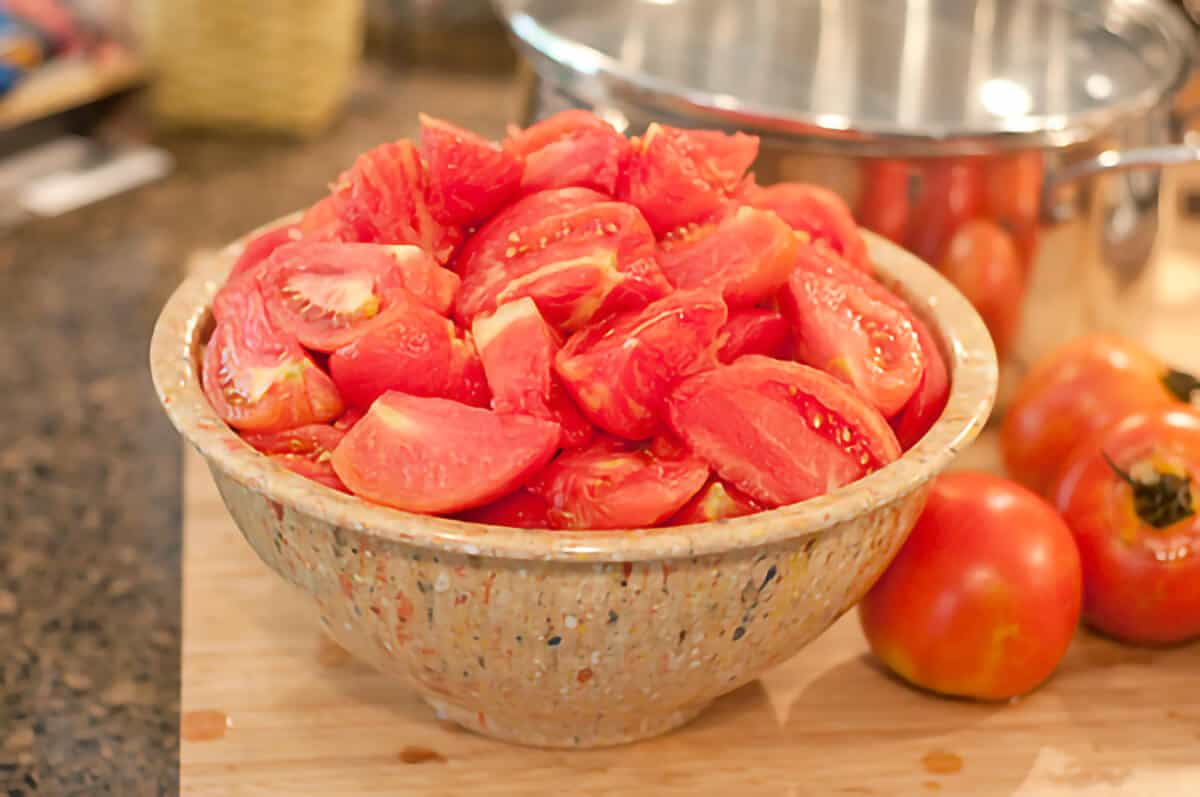 Large bowl heaped full of tomatoes prepared and ready for canning.