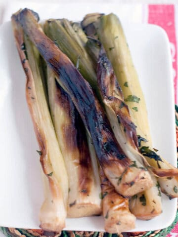 Oven Roasted Leeks on a white serving dish.