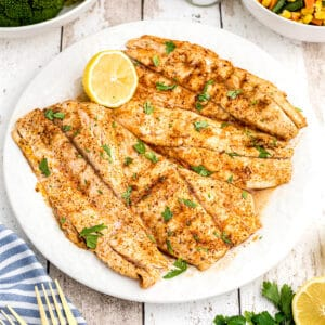 Grilled fish with lemon and parsley on a serving plate.