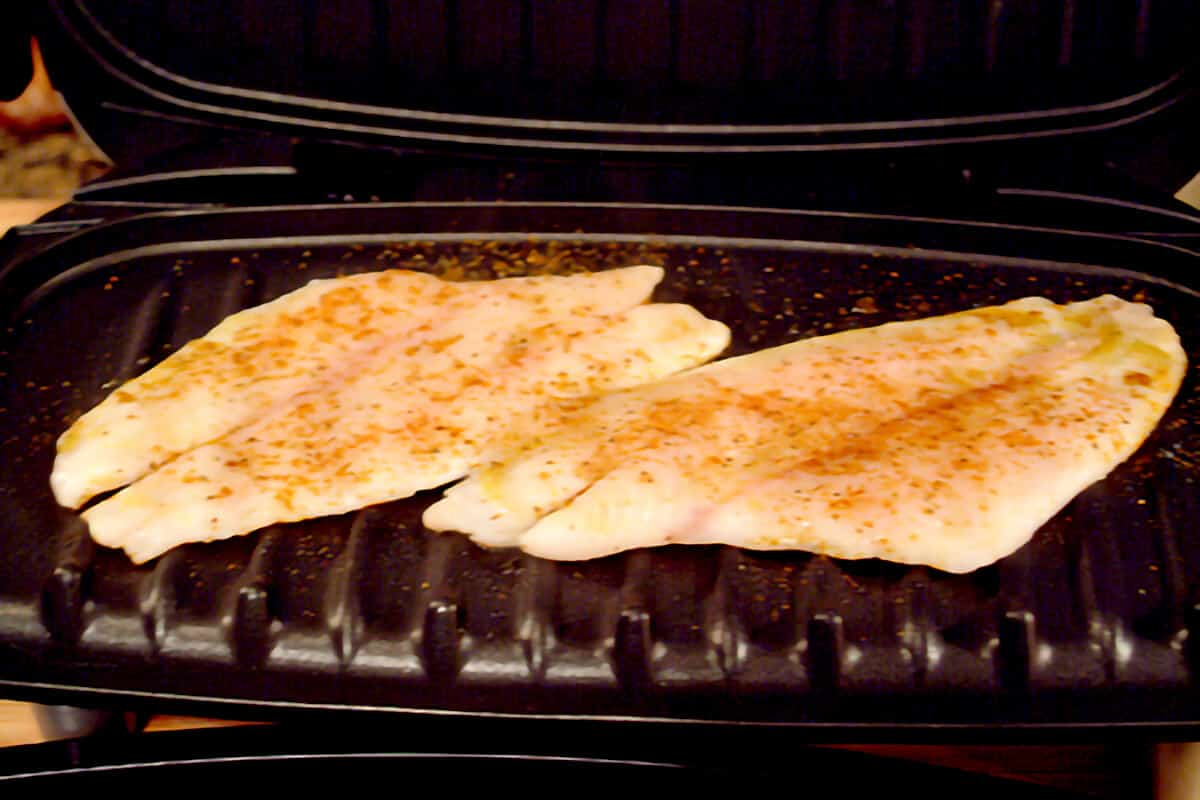 Cooking seasoned fish Ffllets on an electric indoor grill.