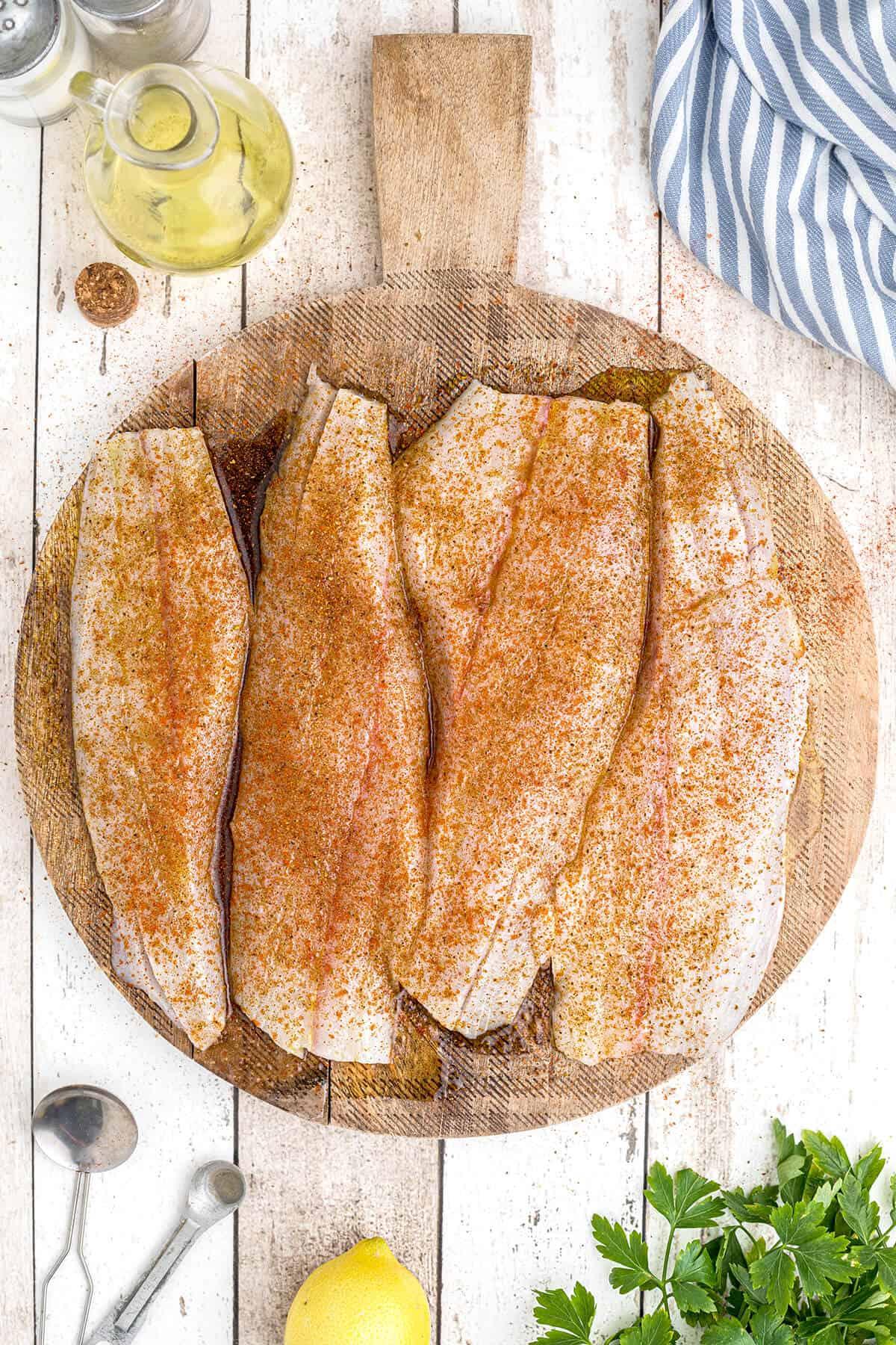 Fish fillets sprinkled with seasonings.