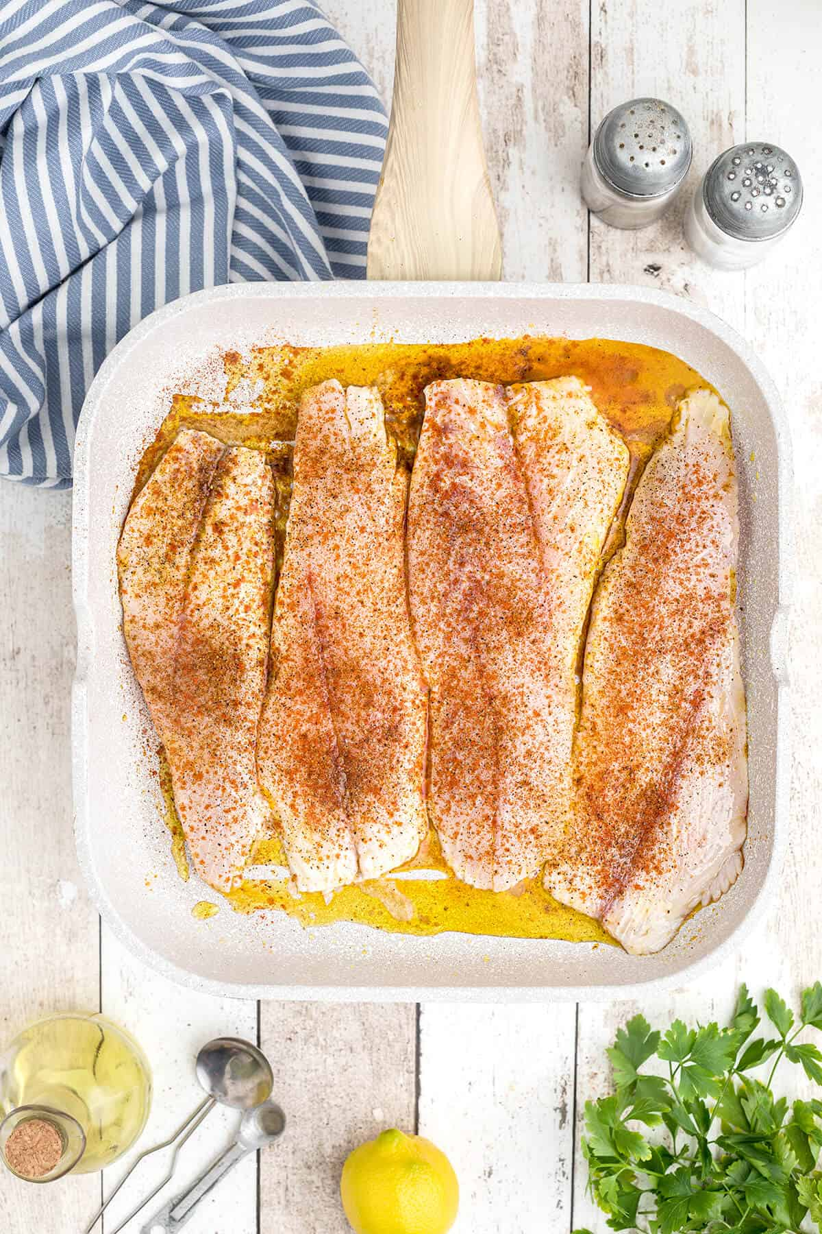 Fish fillets with seasoning applied on a grill pan.