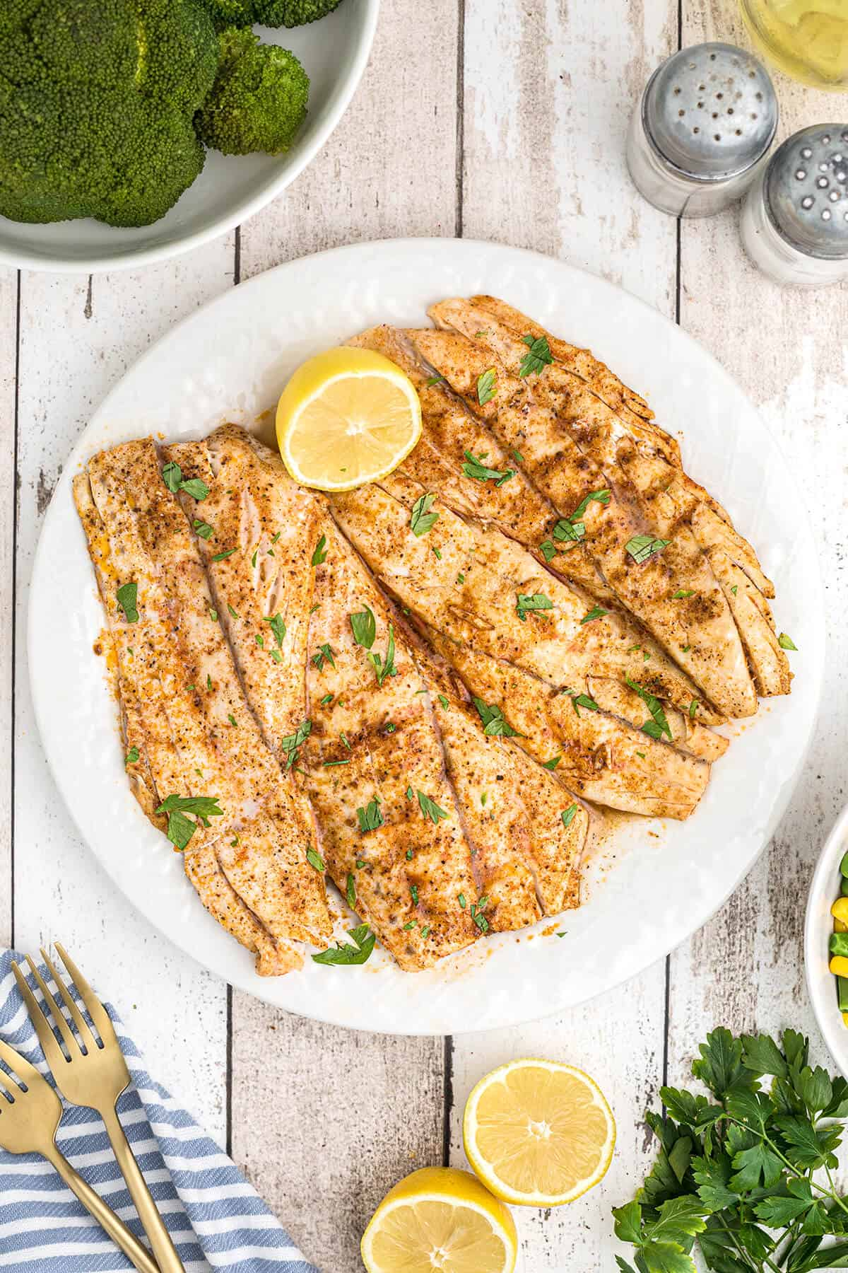 Cooked fish fillets on a plate with a lemon half.