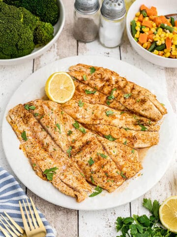 Grilled fish on a white serving plate.