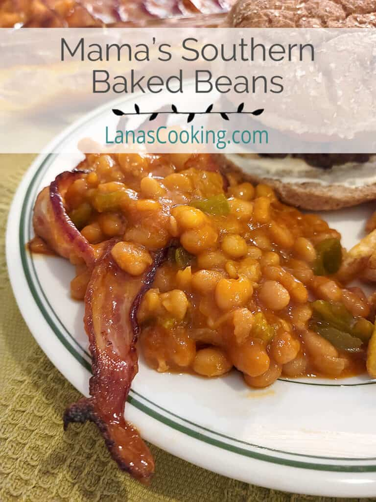 Baked beans and bacon on a plate with a hamburger.