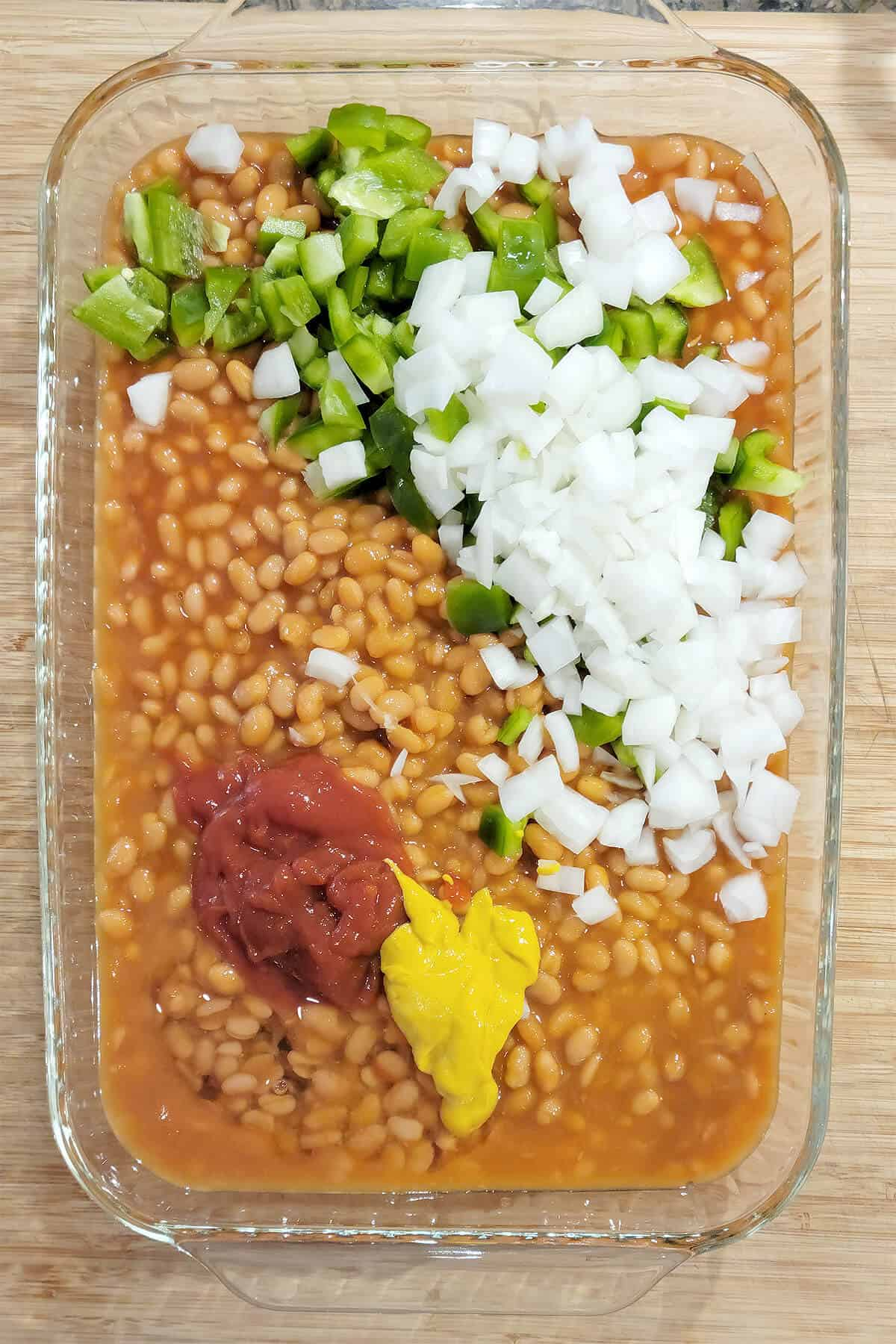 Onions, bell pepper, ketchup, mustard, and syrup added to dish with the beans.