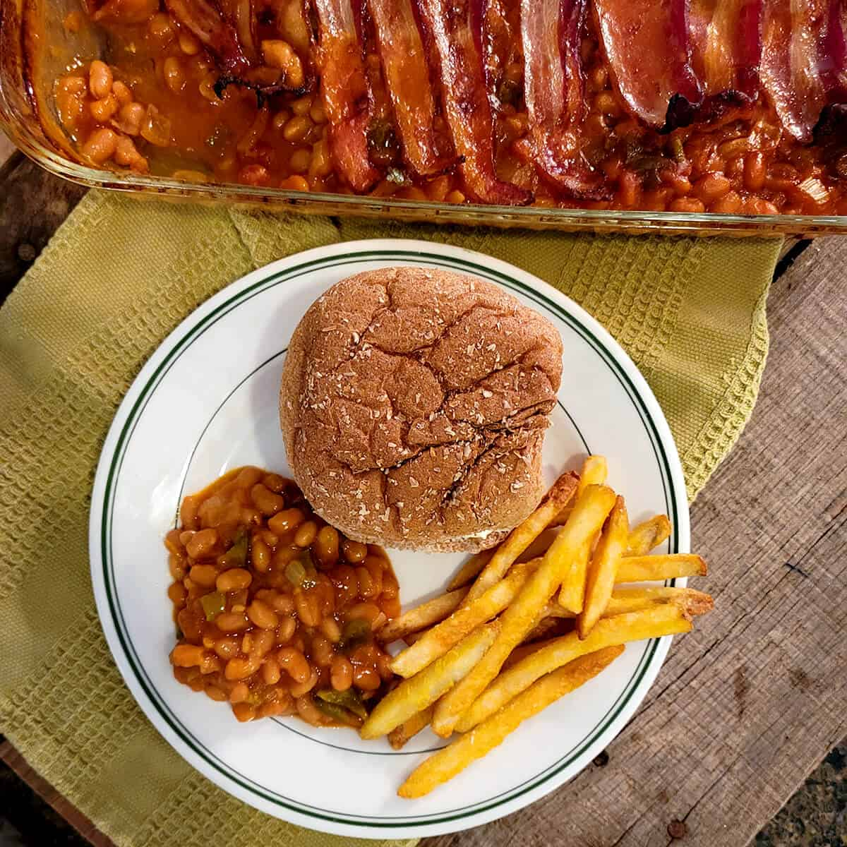 Baked beans and bacon on a plate with a hamburger and fries.