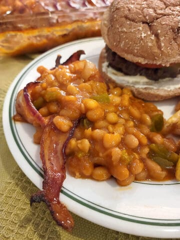 A serving of baked beans with bacon on a plate with a hamburger.