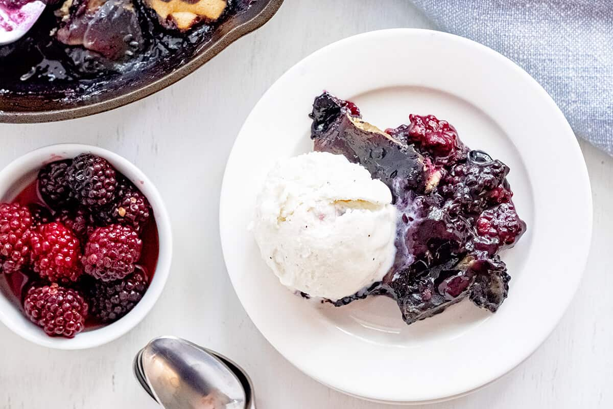 A serving of blackberry cobbler with ice cream on a white plate.