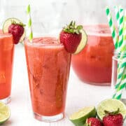 Two glasses of strawberry lemon limeade with a pitcher in the background.