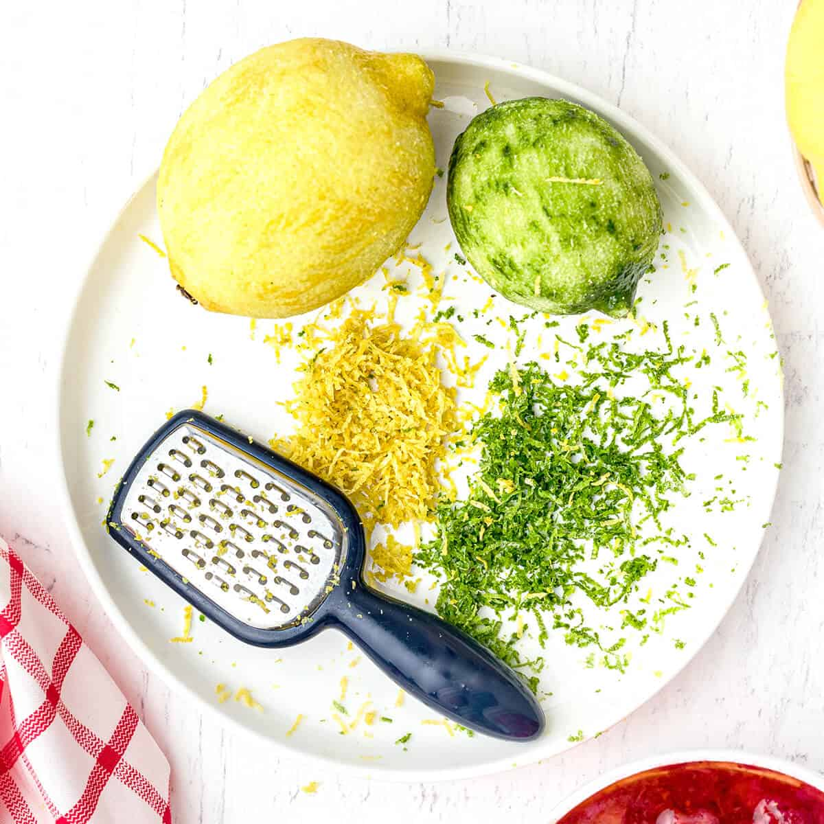 Lemon and lime zest on a plate with a grater.