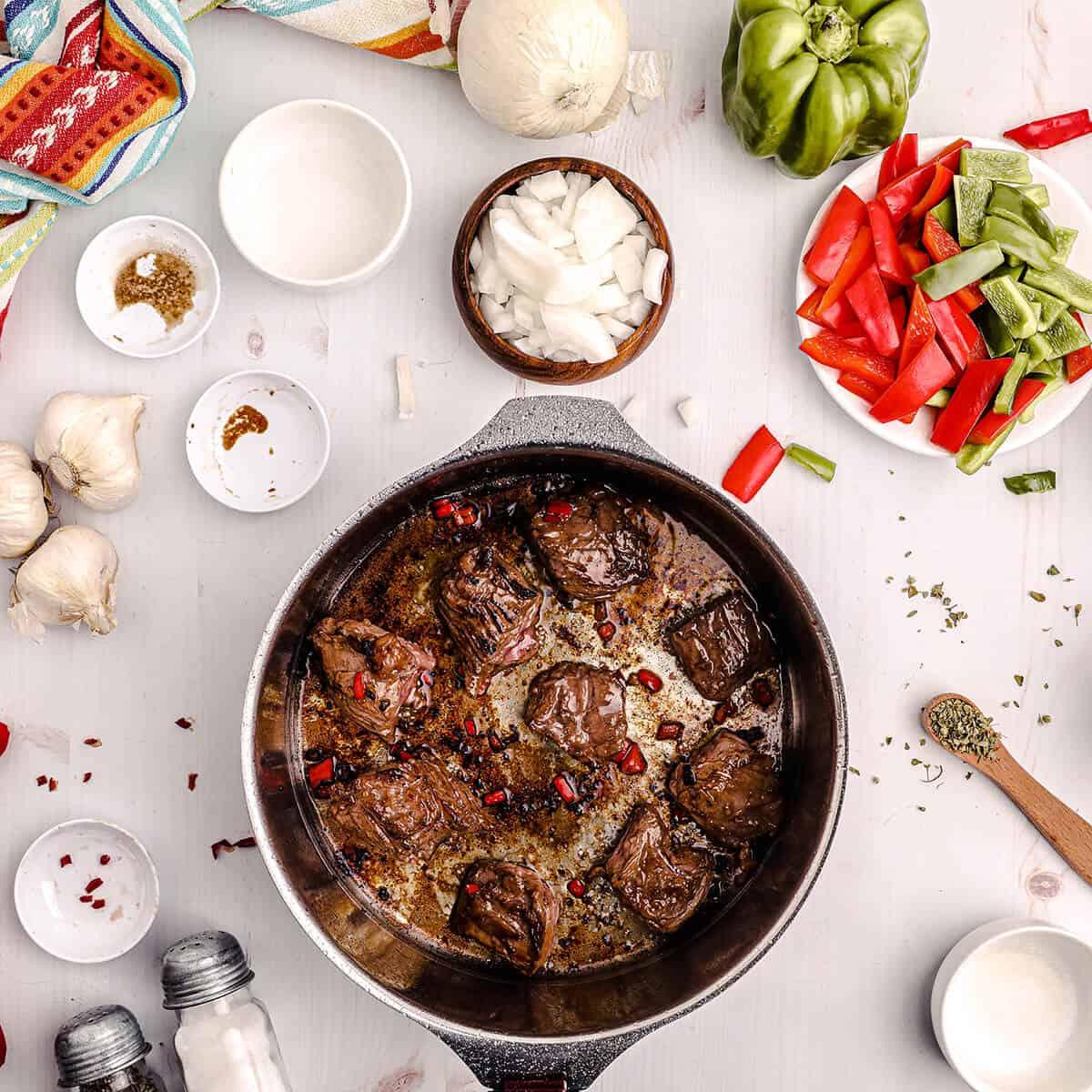 Searing skirt steak in a heavy pan.
