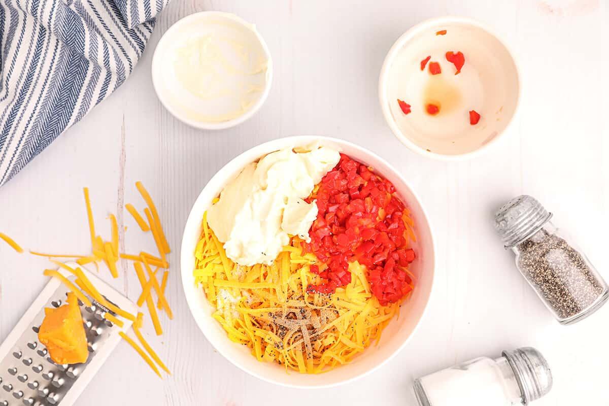 Grated cheese, mayo, and pimientos in a bowl.