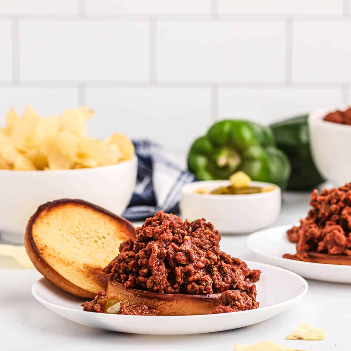 Assembled sloppy joe sandwich on a serving plate with pickles and chips.