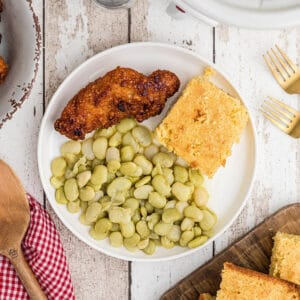Butter beans on a plate with fried chicken and cornbread.