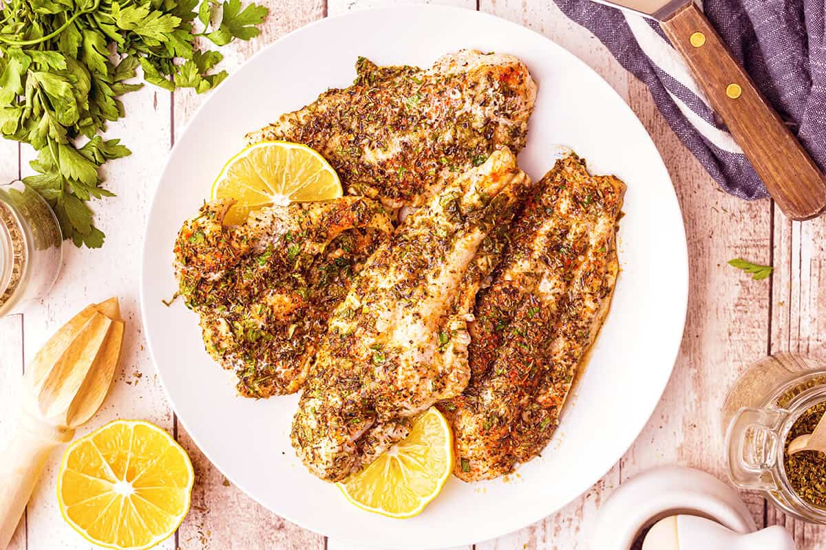 Finished baked catfish on a serving plate.