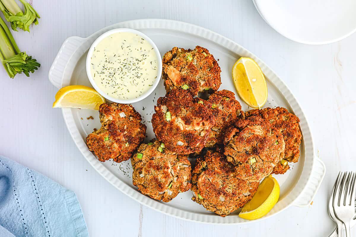 Finished salmon croquettes on a white serving platter.