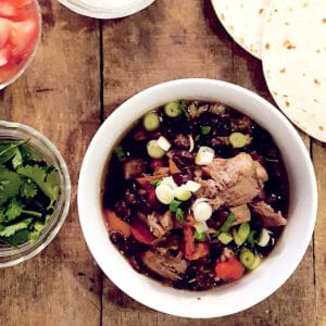 Slow Cooker Pork and Black Bean Stew in a serving bowl with garnishes on the side.