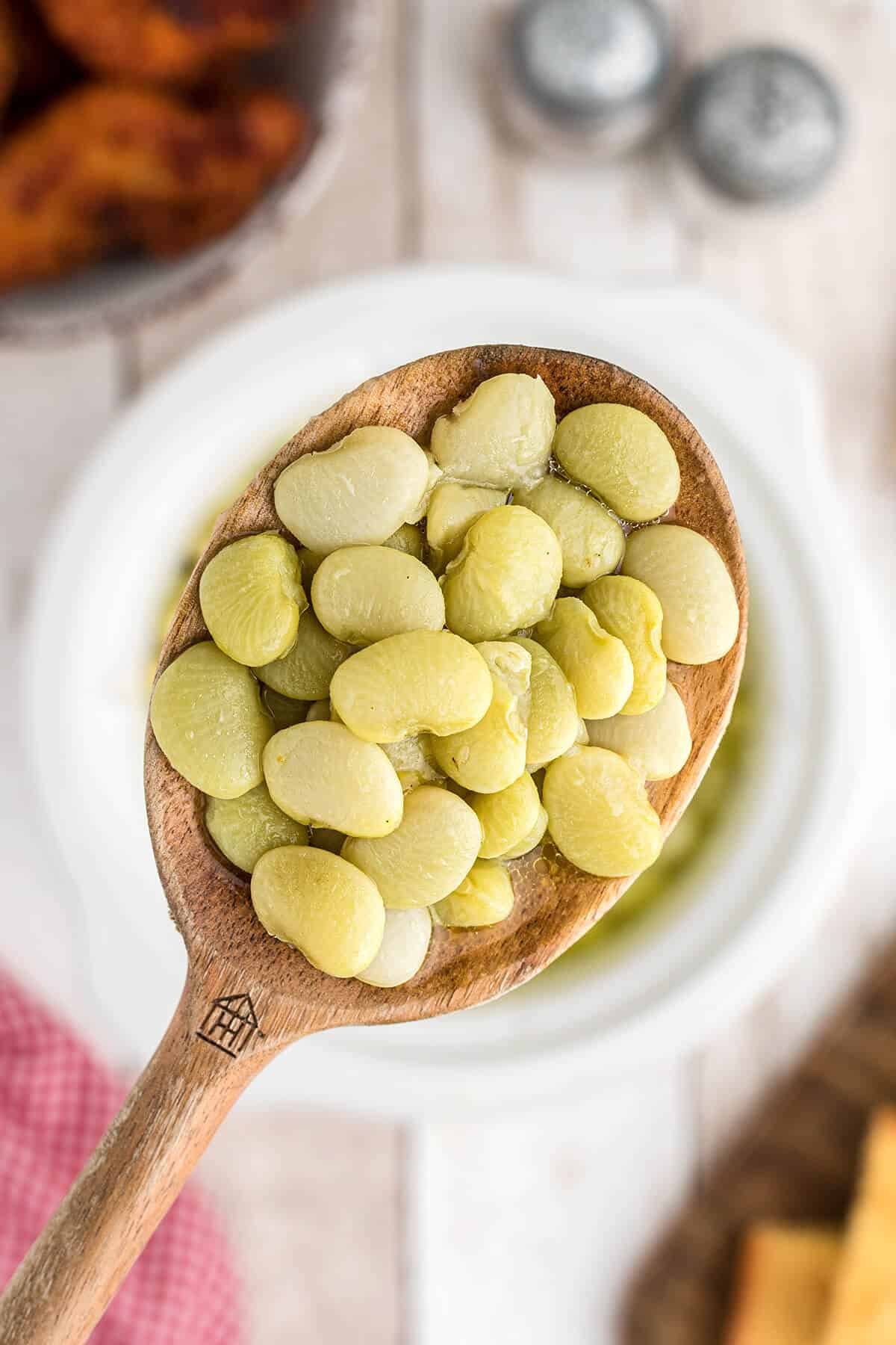Butter beans in a wooden spoon.