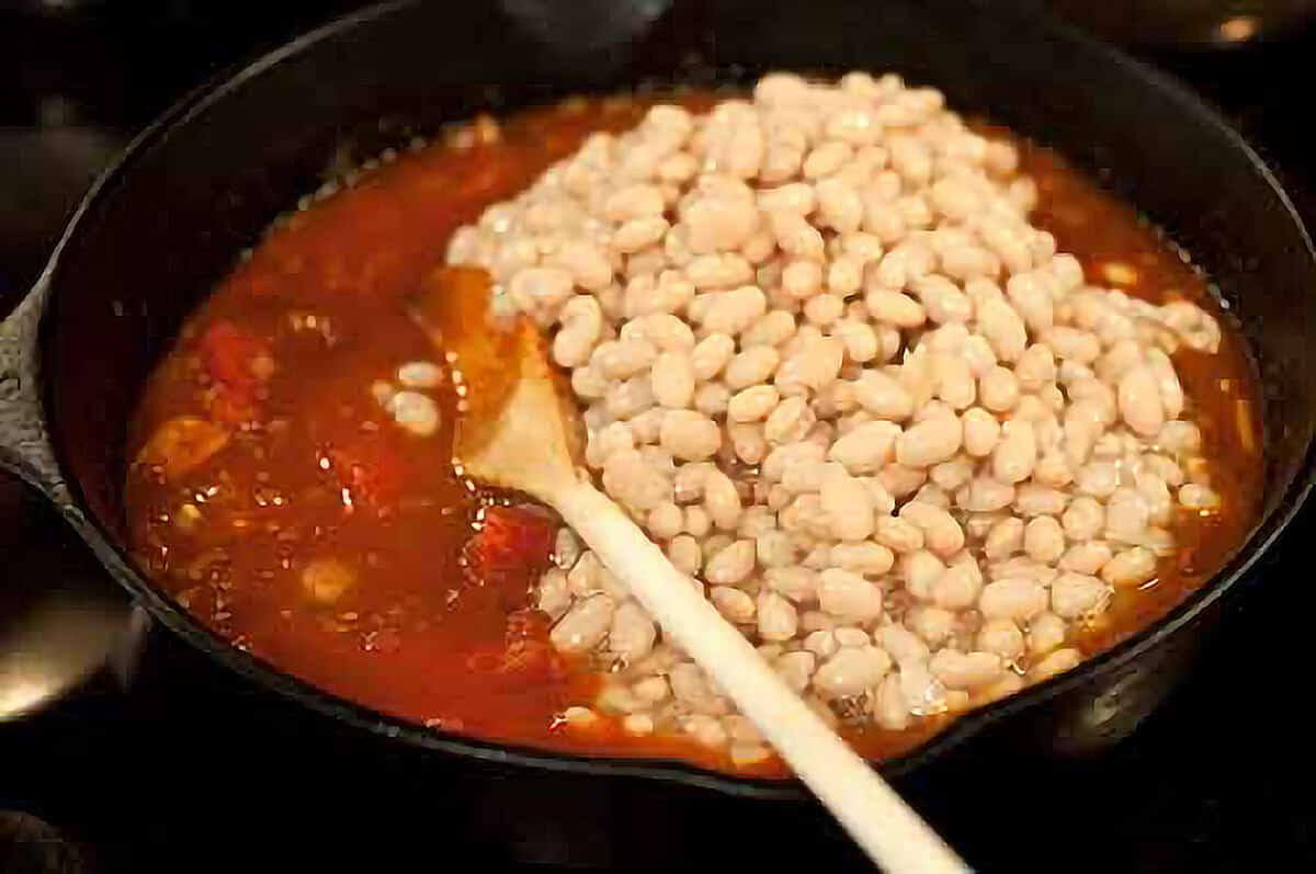 Tomatoes and beans added to the skillet.