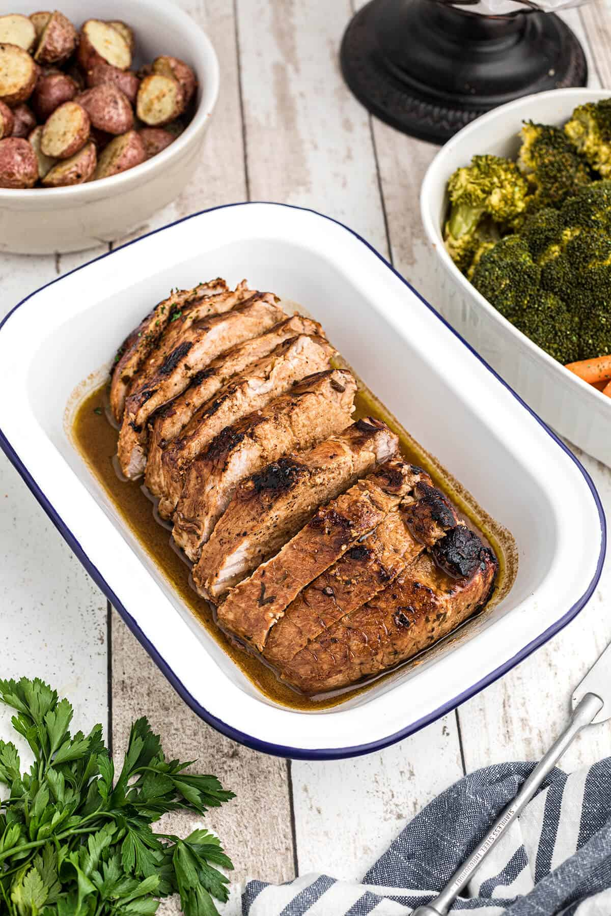 Finished pork loin with sauce in a serving dish.